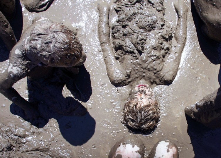 "Kellan Clegg (right), age 9, of Livonia, Michigan, gets covered in mud by his friends while playing in a giant lake of mud at the 25th annual ""Mud Day."" (Bill Pugliano/Getty Images)"