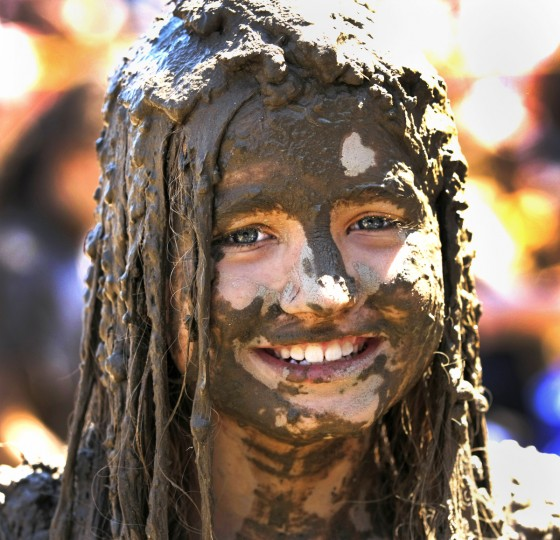 "Elly Kuzma, age 10, of Woodhaven, Michigan is covered with mud while playing in a giant lake of mud at the 25th annual ""Mud Day."" (Bill Pugliano/Getty Images)"