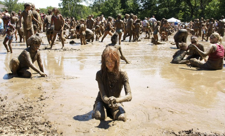 "Alanna Gleason, age 9, of Highland, Michigan plays in a giant lake of mud at the 25th annual ""Mud Day"" in Westland, Michigan. The event, which features a 75' by 150' pit filled with 20,000 gallons of water and 200 tons of topsoil, draws about a thousand children each year. (Bill Pugliano/Getty Images)"