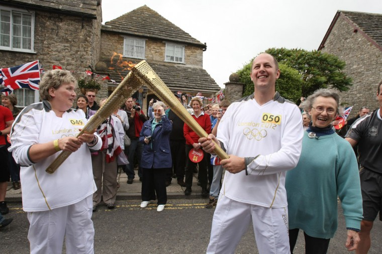 JULY 13: Torchbearer 049 Valerie Mylechreest passes the Olympic Flame to Torchbearer 050 Dean Lightwood as they stand with Penny Elsom (right), the Daughter of Commander Bill Collins who was chief organiser of the 1948 Olympic Torch Relay, outside his former home in Corfe Castle, during Day 56 of the London 2012 Olympic Torch Relay in Dorset, England. (LOCOG via Getty Images)