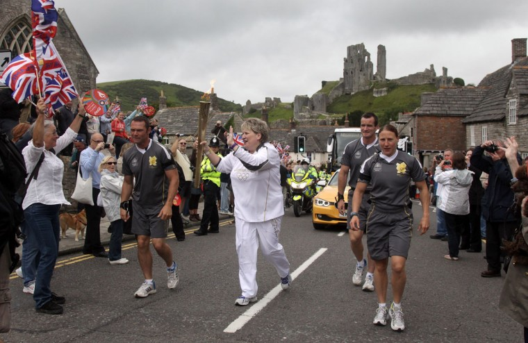 JULY 13: Torchbearer 049 Valerie Mylechreest carries the Olympic Flame on the Torch Relay as Corfe Castle stands in the background, during Day 56 of the London 2012 Olympic Torch Relay in Dorset, England. (Matt Cardy/Getty Images)