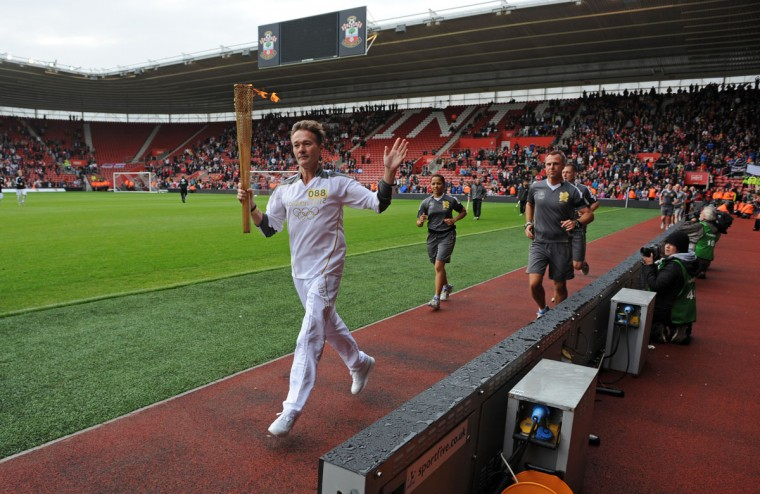 JULY 14: A runner carries the Olympic Flame before the Markus Liebherr Memorial Cup match between Arsenal and Anderlecht at St Mary's Stadium on July 14, 2012 in Southampton, England. (Steve Bardens/Getty Images)