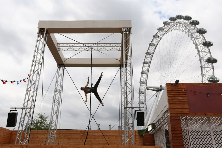 """Mozes"" practices his trapeze routine at the Priceless London Wonderground at the Southbank Centre on July 19, 2012 in London, England. (Oli Scarff/Getty Images)"