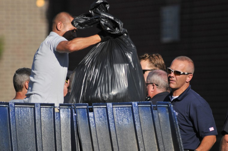 """Police go through the trash near the apartment of of James Holmes, the suspect of a shooting in a movie theater July 20, 2012 in Aurora, outside of Denver, Colorado. According to reports, 12 people have been killed and at least 38 wounded when James allegedly opened fire inside the a movie theater showing the """"The Dark Knight Rises."""" Police have James, 24, of Holmes of North Aurora, in custody. (Thomas Cooper/Getty Images)"""