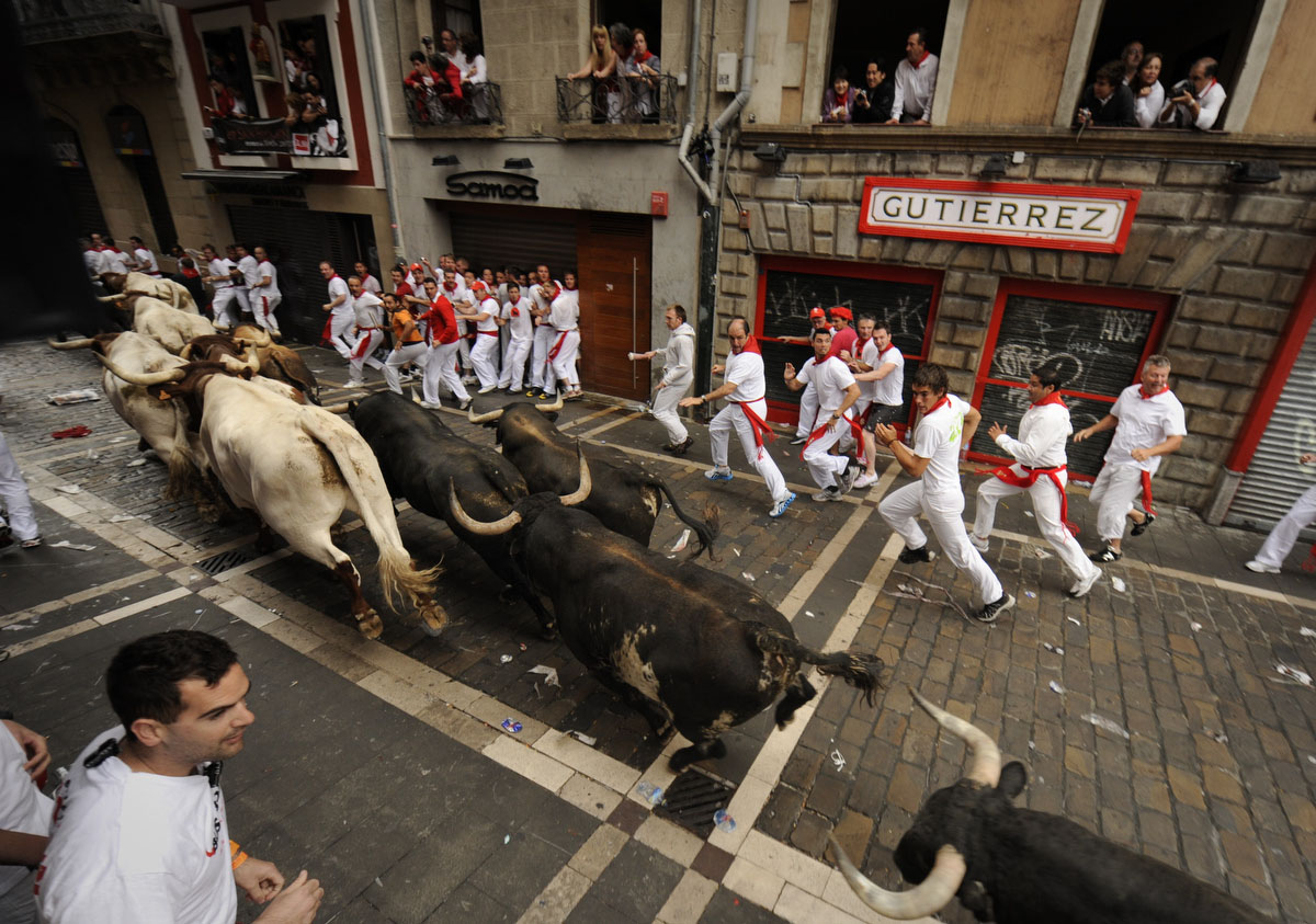 Participants run with Torrestrella's fighting bulls during the first San Fermin Festival bull run, on July 07, 2011, in Pamplona, northern Spain. The festival is a symbol of Spanish culture that attracts thousands of tourists. (Pedro Armestre/Getty Images)