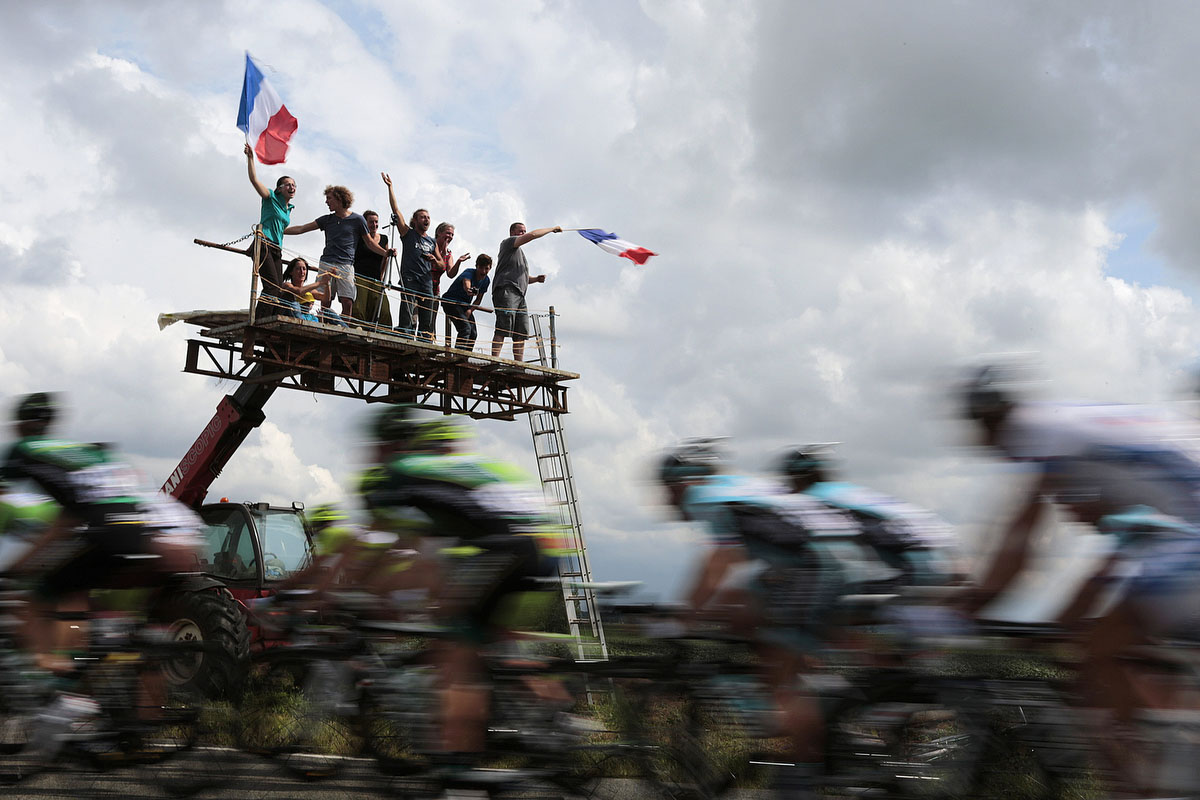 Fans wave a French flag as the pack rides in the 196,5 km and fifth stage of the 2012 Tour de France cycling race starting in Rouen and finishing in Saint-Quentin, northeastern France. (Joel Saget/Getty Images)