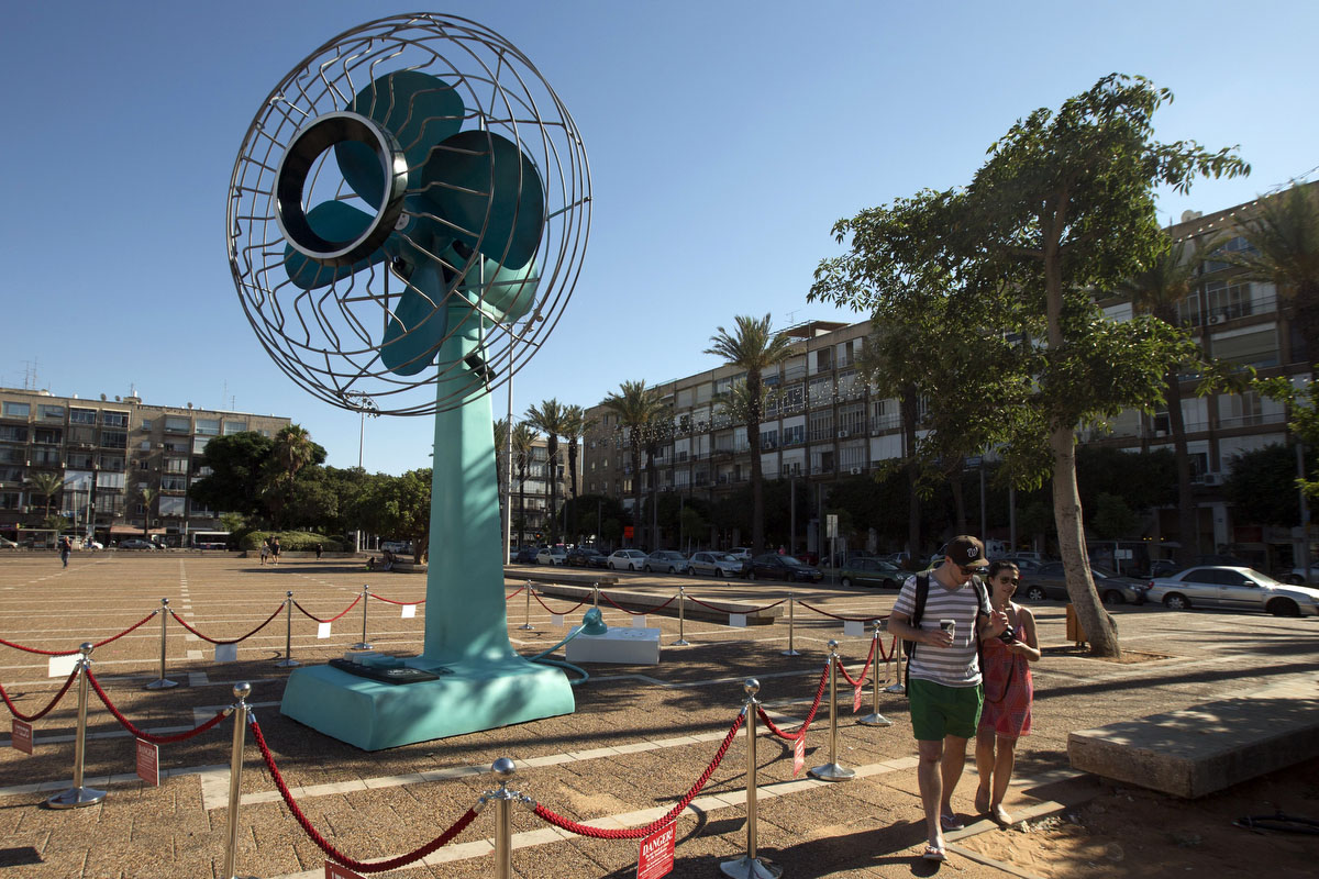 A couple walk past a giant fan installation, created by artist Tal Tenne Czaczkes, which is being exhibited in Rabin Square, near the city hall, in the Mediterranean coastal city of Tel Aviv. The fan measures six metres tall and it runs for two minutes every half-hour. (Jack Guez/Getty Images)