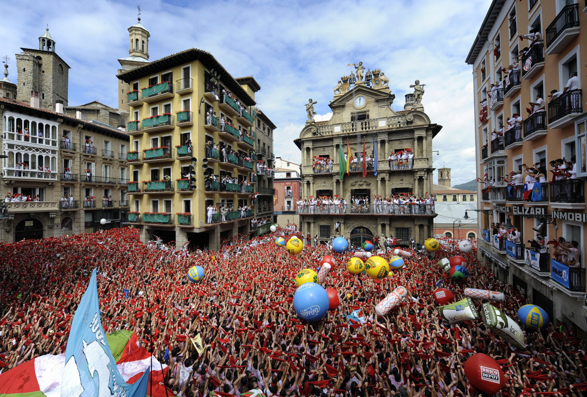 Participants celebrate during the 'Chupinazo' to mark the start at noon sharp of the San Fermin Festival on July 6, 2012 in front of the Town Hall of Pamplona, northern Spain. Tens of thousands of people packed Pamplona's streets for a drunken kick-off to Spain's best-known fiesta: the nine-day San Fermin bull-running festival. (Rafa Rivas/GettyImages)