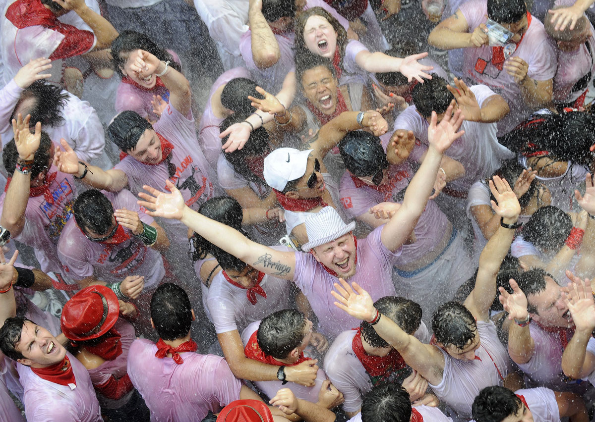 Participants are sprayed with water as they celebrate during the 'Chupinazo' to mark the start at noon sharp of the San Fermin Festival on July 6, 2012 in front of the Town Hall of Pamplona, northern Spain. (Rafa Rivas/Getty Images)
