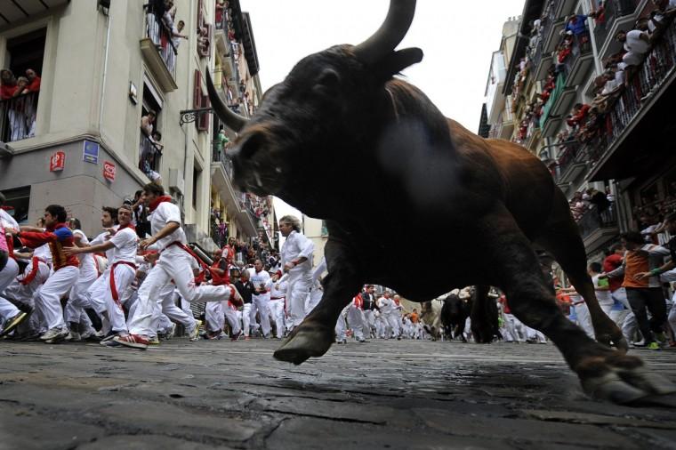 Participants run in front of Cebada Gago bulls during the third bull run of the San Fermin festival. (Rafa Rivas/Getty Images)