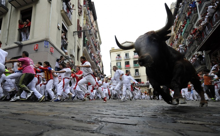 Participants run in front of Cebada Gago bulls during the third bull run of the San Fermin festival in the Northern Spanish city of Pamplona. The festival is a symbol of Spanish culture that attracts thousands of tourists to watch the bull runs despite heavy condemnation from animal rights groups . (Rafa Rivas/Getty Images)