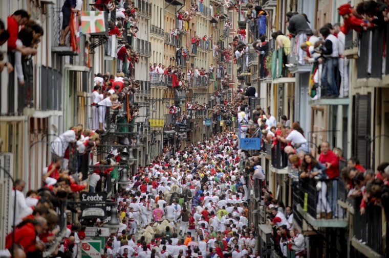 Participants run in front of Fuente Ymbro's bulls during the fifth San Fermin Festival bull run in Pamplona, northern Spain. The festival is a symbol of Spanish culture that attracts thousands of tourists to watch the bull runs despite heavy condemnation from animal rights groups. (Pedro Armestre/GettyImages)