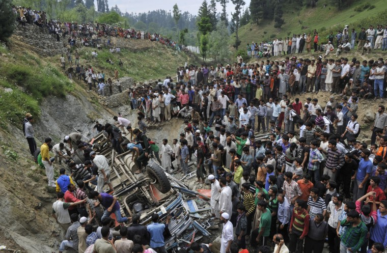 Kashmiri villagers stand near the wreckage of a bus at Nambal Nard some 55 kms northwest of Srinagar. A teacher and a student were killed and 51 others injured when a school bus carrying students on a picnic trip fell into a gorge near the Gulmarg tourist resort in Kashmir's Baramulla district. The bus carrying students to Baba Reshi shrine near Gulmarg fell into the gorge at Nambal Nard near Tangmarg, 45 kms from here, a police officer said. (Tauseef Mustafa/GettyImages)
