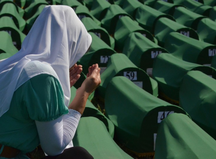 A Bosnian muslim woman prays among 520 body caskets laid out in preparation for a mass burial ceremony at the Srebrenica-Potocari Memorial Cemetery in Potocari. Tens of thousands of people arrived in Potocari on July 11 to commemorate the 17th anniversary of the moment the UN-protected enclave fell to Bosnian Serb troops. The remains of 520 people will be buried alongside the 5,137 victims of the massacre already buried in the vast cemetery which faces the former UN army base. Some 8,000 Muslim men and boys were killed in just a few days after the eastern town under UN protection was captured by Bosnian Serb forces 17 years ago. (Elvis Barukcic/GettyImages)