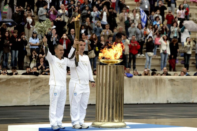 MAY 17: The last torchbearers Olympic gold medalist Pyrros Dimas (R) and Li Ning carry the Olympic flame at the Panathinaiko stadium during the Olympic Torch Handover Ceremony, on May 17, 2012 in Athens, Greece. (Milos Bicanski/Getty Images)