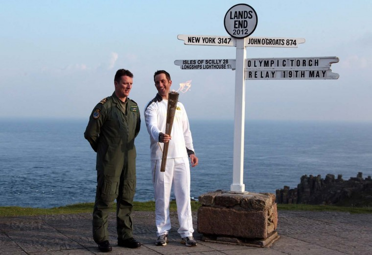 MAY 19: Olympic gold medal sailor and the first London 2012 torchbearer, Ben Ainslie and lieutenant commander Richie Full, who delivered the Olympic Flame from RNAS Culdrose, pose for a photograph beside the Lands End sign on May 19, 2012 in Cornwall, England. The Olympic Flame arrived in the UK today and now begins a 70-day relay involving 8,000 torchbearers covering 8,000 miles. (Matt Cardy/Getty Images)