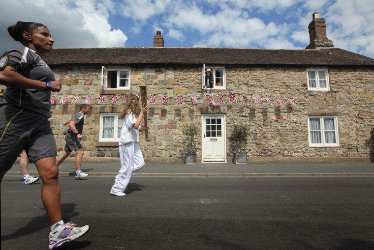 MAY 30: Resident Gabrielle Drake looks out of the window of Hollybush Cottage as the Olympic Torch passes through Much Wenlock. Much Wenlock is the birthplace and former home of William Penny Brookes, who is considered the founding father of the modern Olympics. (Christopher Furlong/Getty Images)