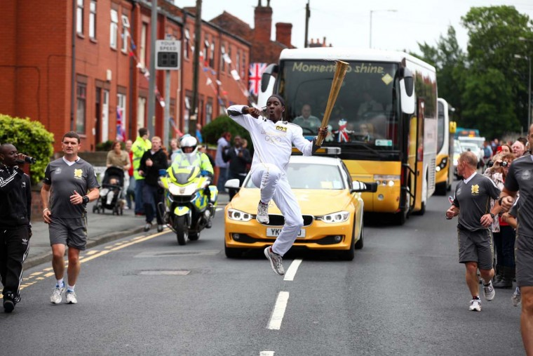 MAY 31: Torchbearer #093 Natimi Black-Heaven carries the Olympic Flame on Day 13 between Lowton and Abram near Lowton, England. (LOCOG via Getty Images)
