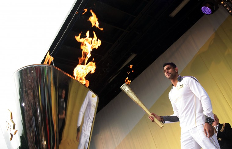 MAY 31: Torchbearer #135 Amir Khan lights the cauldron with the Olympic Flame at the end of the Torch Relay leg through Bolton on Day 13 of the London 2012 Olympic Torch Relay in Bolton, England. (LOCOG via Getty Images)