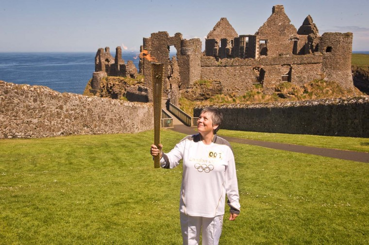 JUNE 4: Torchbearer 005, Jean Jones holds the Olympic Flame aloft in front of Dunluce Castle on Day 17 of the London 2012 Olympic Torch Relay. (LOCOG via Getty Images)