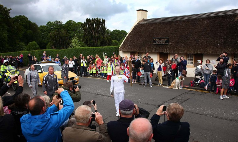JUNE 08: Torchbearer #038 Ida Ahlbom holds the Olympic Flame in front of Burns Cottage, the first home of Robert Burns, during Day 21 of the London 2012 Olympic Torch Relay in Alloway, United Kingdom. (LOCOG via Getty Images)