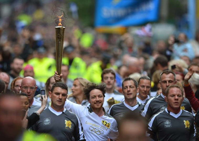 JUNE 08: Actor James Mcavoy runs down Buchanan Street carrying the Olympic Torch during the leg between Stranrear and Glasgow on June 8, 2012 in Glasgow, Scotland. (Jeff J Mitchell/Getty Images)