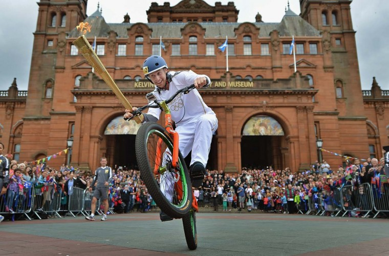 JUNE 08: Stunt cyclist Danny MacAskill rides with the Olympic Torch outside Kelvingrove Art Grove Art Gallery during the leg between Stranrear and Glasgow in Glasgow, Scotland. (Jeff J Mitchell/Getty Images)