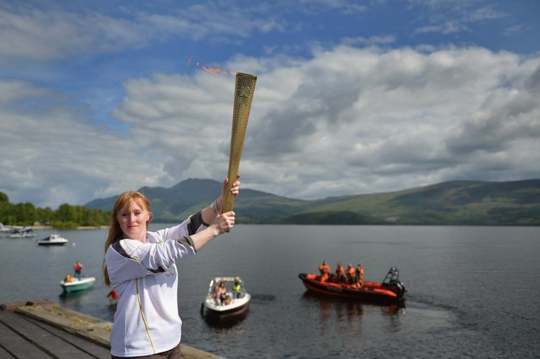 JUNE 09: Shelia McNeil holds the Olympic Flame as it passes through the village of Luss on the banks of Loch Lomond in Luss, Scotland. (Jeff J Mitchell/Getty Images)