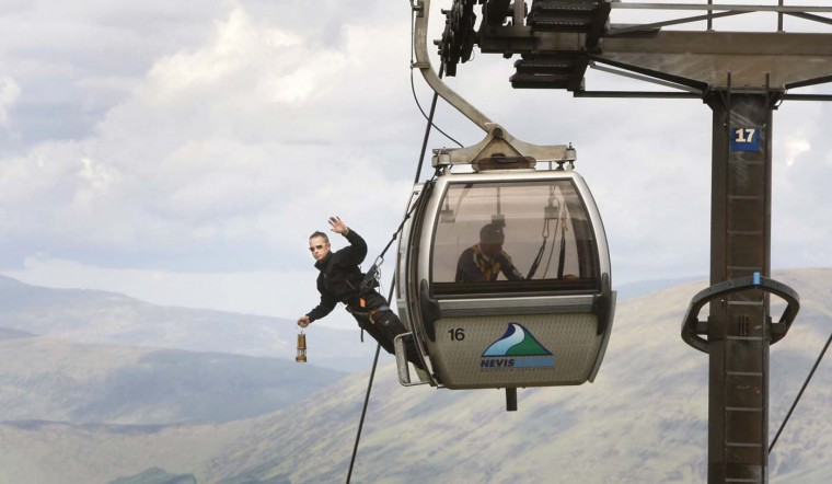 JUNE 9: Employee of the Nevis Range Davie Austin carries the Olympic Flame on a gondola on the Nevis Range on Day 22 of the London 2012 Olympic Torch Relay in Scotland, United Kingdom. (LOCOG via Getty Images)