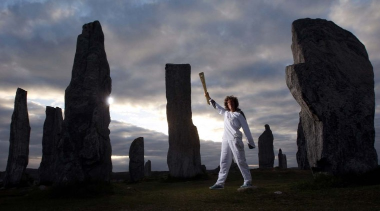 JUNE 11: Torchbearer #003 Kirsty Wade holds the Olympic Flame at the Calanais Standing Stones in Callanish as the sun rises on Day 24 of the London 2012 Olympic Torch Relay in Lewis, Scotland. (LOCOG via Getty Images)