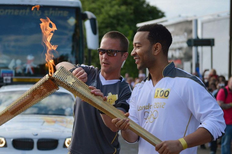 JUNE 13: Singer songwriter John Legend carries the Olympic Torch during the London 2012 Olympic Torch Relay in Edinburgh, Scotland. (Jeff J Mitchell/Getty Images)