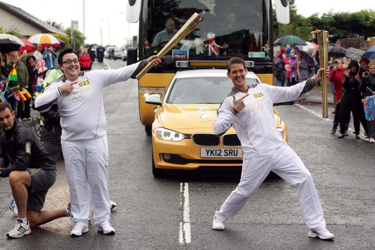 JUNE 21: Torchbearer #020 Calum Graham passes the Olympic Flame to Torchbearer #021 Paul Mcghee on the Torch Relay leg between Annan and Gretna on June 21, 2012 in Gretna, Scotland. (LOCOG via Getty Images)