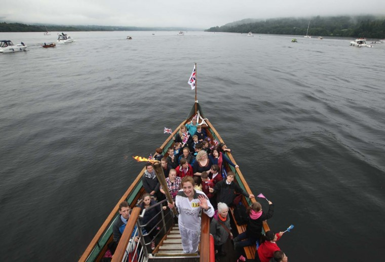 JUNE 21: Torchbearer Stephanie Booth, 14, from Windermere carries the Olympic flame on board historic steam boat The Tern during a voyage across Lake Windermere in Windermere, England. (Christopher Furlong/Getty Images)