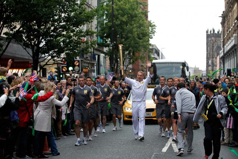 JUNE 23: Torchbearer and British cyclist Sir Chris Hoy carries the Olympic Flame on the Torch Relay leg between Lytham St. Anne's and Manchester. (Paul Thomas/Getty Images)