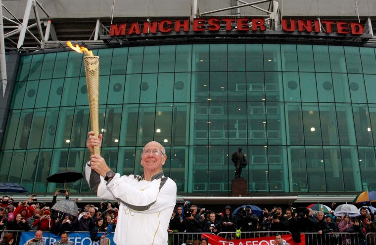 JUNE 24: Ex-Manchester United and England football player Sir Bobby Charlton carries the Olympic Flame on the Torch Relay leg between Salford and Leeds in Manchester, England. (Paul Thomas/Getty Images)