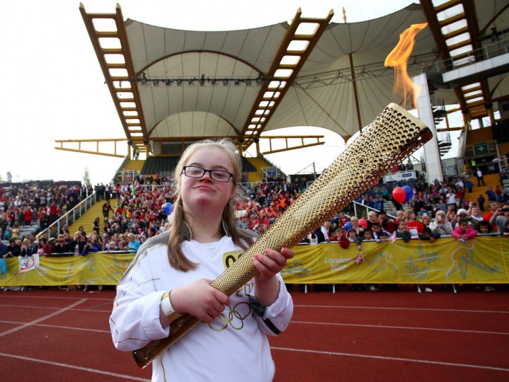 JUNE 26: Torchbearer Lucy Brunt holds the Olympic Flame on the running track of Don Valley Stadium during Day 39 of the London 2012 Olympic Torch Relay in Sheffield, England. (LOCOG via Getty Images)