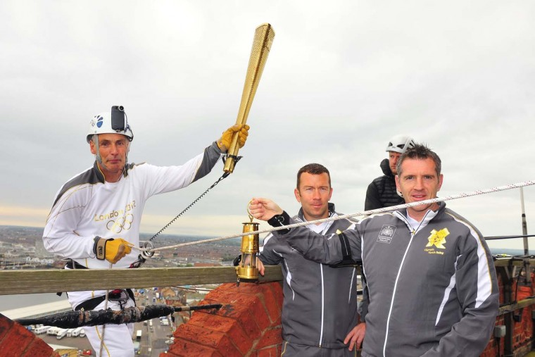 JUNE 27: Torchbearer Alan Ellinson holds the Torch before he abseils with the Olympic Flame down the side of the Royal Dock Tower in Grimsby at the beginning of Day 40 of the London 2012 Olympic Torch Relay in Grimsby, England. (LOCOG via Getty Images)