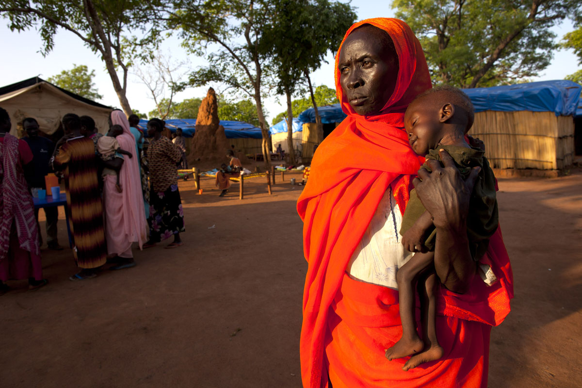 JUNE 29: A woman holds her grandson at a malnutrition and feeding center at the Yida refugee camp along the border with North Sudan June 29, 2012 in Yida, South Sudan. Yida refugee camp has swollen to nearly 60,000, as the refugees flee from South Kordofan in North Sudan. The rainy season has increased the numbers of sick children suffering from Diarrhea and severe malnutrition as the international aid community struggles to provide basic assistance to the growing population, most have arrived with only the clothes they are wearing. Many new arrivals walked from 5 days up to 2 weeks or more to reach the camp. (Paula Bronstein/Getty Images)