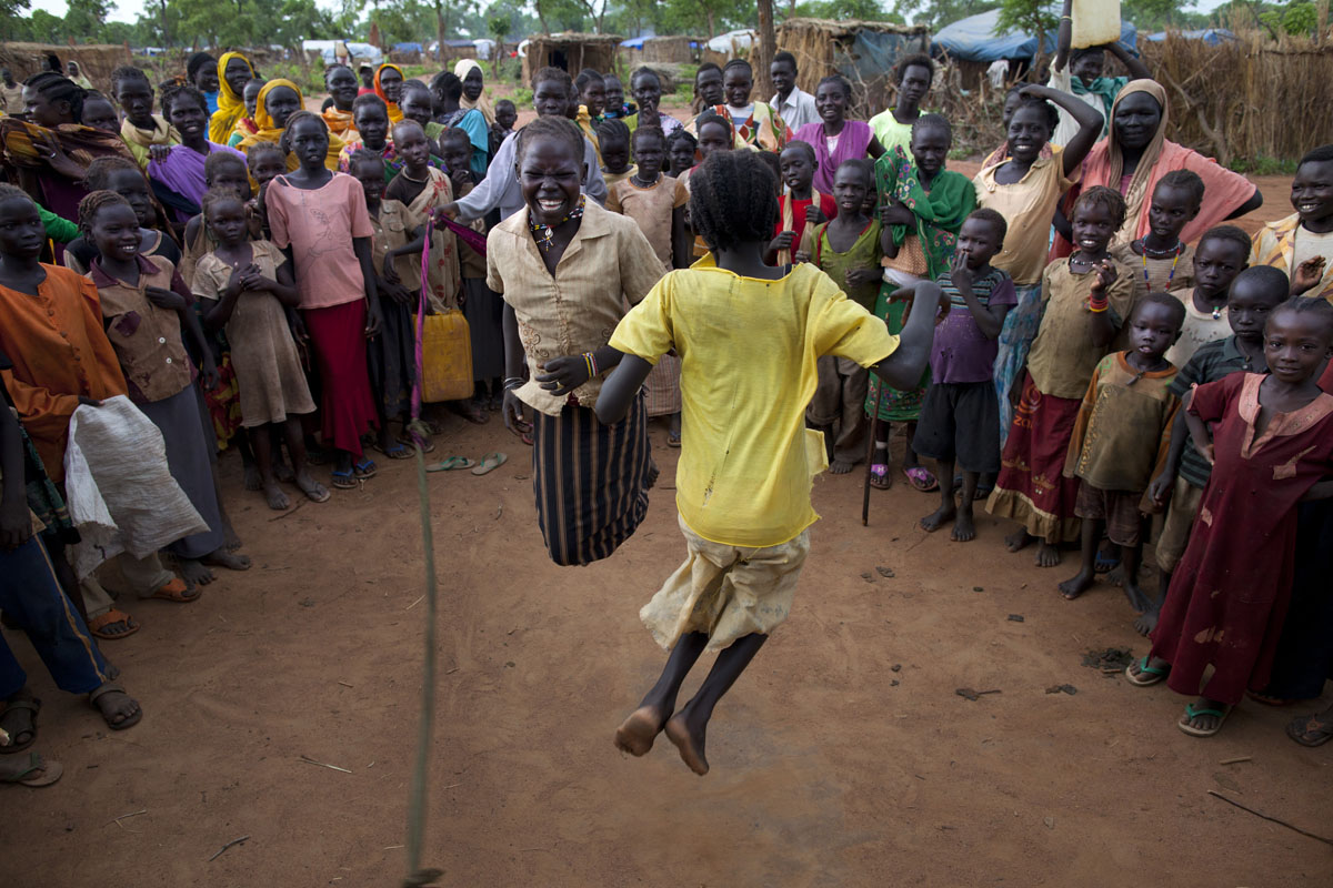 JUNE 30: Sudanese girls jump rope as many look on at the Yida refugee camp along the border with North Sudan June 30, 2012 in Yida, South Sudan. Water has been a precious resource that aid agencies have struggled with. Yida refugee camp has swollen to nearly 60,000, as the refugees flee from South Kordofan in North Sudan with new arrivals at 300-600 a day. The rainy season has increased the numbers of sick children suffering from Diarrhea and severe malnutrition as the international aid community struggles to provide basic assistance to the growing population, most have arrived with only the clothes they are wearing. Many new arrivals walked from 5 days up to 2 weeks or more to reach the camp. (Paula Bronstein/Getty Images)