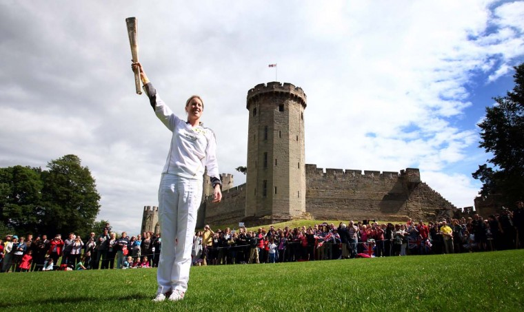 JULY 1: Torchbearer #119 Georgina Harland holds the Olympic Flame in front of Warwick Castle during Day 44 of the Olympic Flame Torch Relay on July 1, 2012 in Warwick, England. (LOCOG via Getty Images)