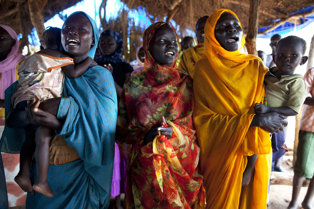 JULY 1: Sudanese refugees rejoice in prayer in a makeshift church at the Yida refugee camp, close to the border with North Sudan, on July 01, 2012 in Yida, South Sudan. The Yida refugee camp has swollen to nearly 60,000, as refugees flee from South Kordofan in North Sudan, with new arrivals at 300-600 a day. The rainy season has increased the numbers of sick children suffering from diarrhea and severe malnutrition, as the international aid community struggles to provide basic assistance to the growing population. Most have arrived with only the clothes they are wearing. Many new arrivals have walked from between 5 days and 2 weeks or more to reach the camp. (Paula Bronstein/Getty Images)