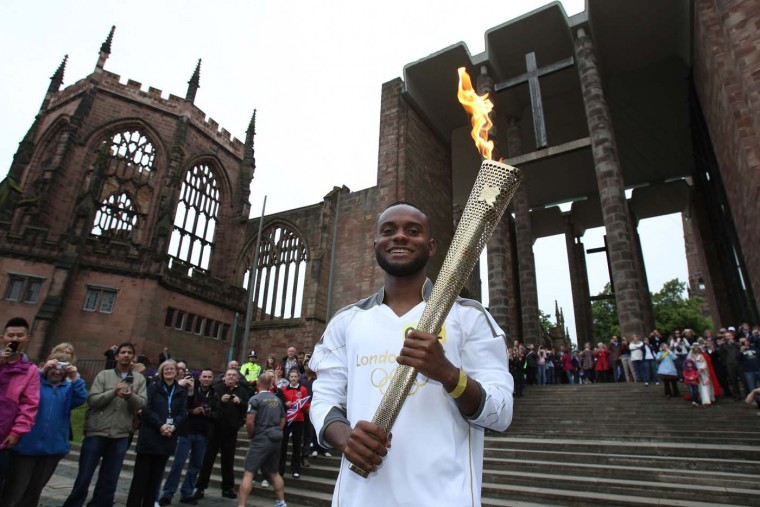 JULY 2: Torchbearer #002 Ali Abdillahi holds the Olympic Flame at the Coventry Cathedral ruins during Day 45 in Coventry, England. (LOCOG via Getty Images)