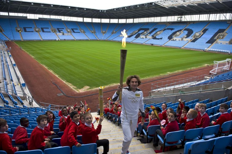 JULY 2: Torchbearer #005 and Trialthlete Tim Don carries the Olympic Flame in the stands of the City of Coventry Stadium during Day 45 in Coventry, England. (LOCOG via Getty Images)