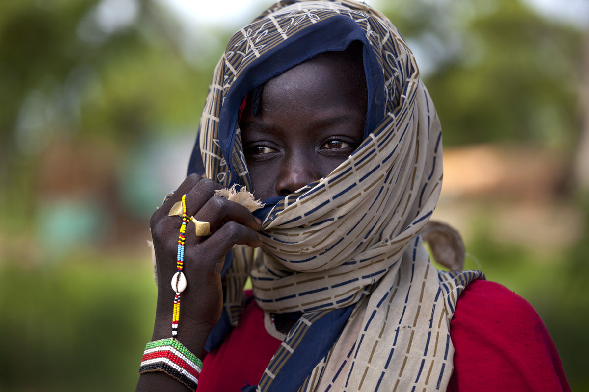 JULY 2: A Sudanese girl hides her face from the hot sun after walking for many hours along the border road after crossing from North Sudan July 2, 2012 in Jaw, South Sudan. Many refugees walk from four days to two weeks, fleeing the on-going conflict, to get to Yida refugee camp from the Nuba mountain region where they have no food. The Yida refugee camp has swollen to nearly 60,000 people as the refugees flee from South Kordofan in North Sudan, with 300-600 people arriving daily. The rainy season has increased the numbers of sick children suffering from Diarrhea and severe malnutrition, as the international aid community struggles to provide basic assistance to the growing population. Most have arrive with only the clothes they are wearing. (Paula Bronstein/Getty Images)