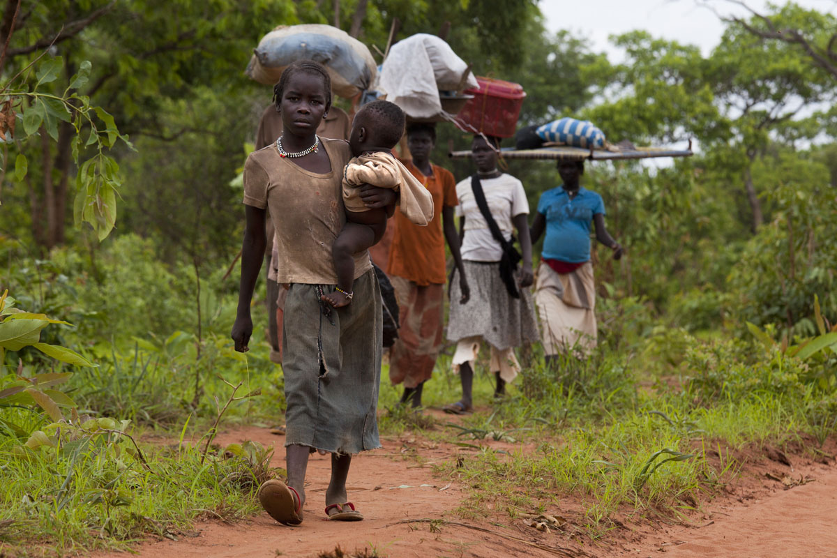 JULY 2: Sudanese refugees walk along the border road after crossing from North Sudan carrying their possessions July 2, 2012 in Jaw, South Sudan. Many refugees walk from four days to two weeks, fleeing the on-going conflict, to get to Yida refugee camp from the Nuba mountain region where they have no food. The Yida refugee camp has swollen to nearly 60,000 people as the refugees flee from South Kordofan in North Sudan, with 300-600 people arriving daily. The rainy season has increased the numbers of sick children suffering from Diarrhea and severe malnutrition, as the international aid community struggles to provide basic assistance to the growing population. Most have arrive with only the clothes they are wearing. (Paula Bronstein/Getty Images)