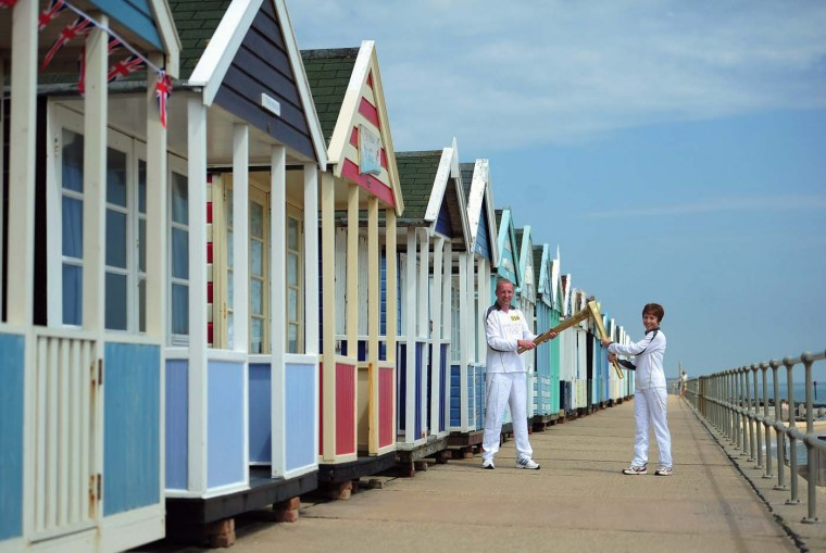 JULY 05: Caroline Emeny and Richard Game carry the Olympic torch past the beach huts on Southwold sea front in Southwold, England. (Jamie McDonald/Getty Images)