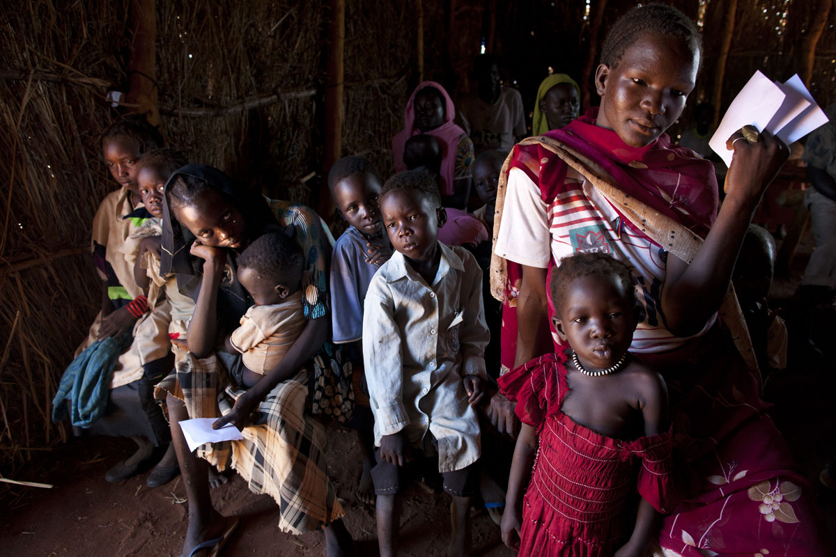 JULY 5: People wait in line for hours to receive medical treatment at the CARE medical clinic at the Yida refugee camp along the border with North Sudan July 5, 2012 in Yida, South Sudan. The number of people arriving at the Yida refugee camp increases every day with the current population exceeding 64,000, as refugees continue to flee South Kordofan in North Sudan. Refugees arriving from the North can number between 500 to 1,000 a day and many have experienced long, arduous journeys without food to reach the camp. The rainy season has increased the numbers suffering from diarrhea, severe malnutrition and malaria. Even with refugees having food, there are sanitation issues causing increasing incidents of illness with the field hospitals saying that 95% of all patients are under the age of five. (Paula Bronstein/Getty Images)