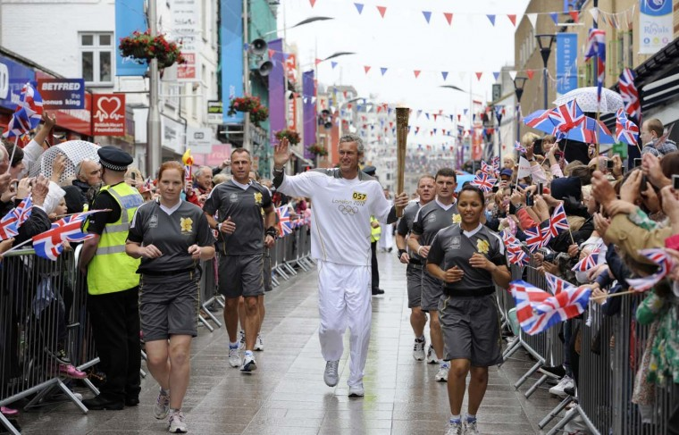 JULY 06: Olympic Swimmer and Torchbearer #057 Mark Foster carries the Olympic Flame through Southend during Day 49 of the London 2012 Olympic Torch Relay in Southend, England. (LOCOG via Getty Images)