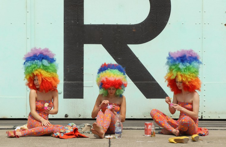 Models take a break outside a former aircraft hangar at Temepelhof Airport at the 2012 Bread & Butter fashion trade fair in Berlin, Germany. Bread & Butter is the world's largest trade fair for street fashion. (Sean Gallup/Getty Images)