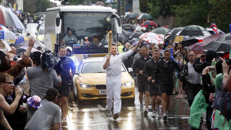 JULY 07: TV Chef and Torchbearer Jamie Oliver carries the Olympic Flame on the Torch Relay journey between Newport and Saffron Walden during Day 50 of the London 2012 Olympic Torch Relay in Newport, England. (LOCOG via Getty Images)